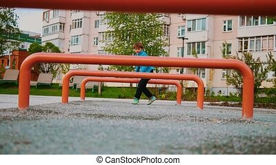 A little boy playing on the playground - jumping over the obstacles
