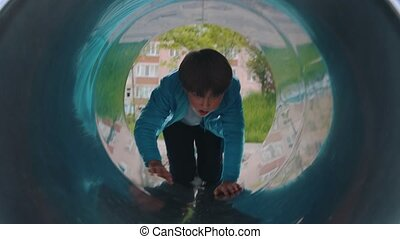 A little boy playing on the playground outside - crawling through the tube