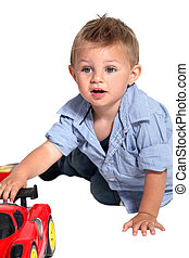 A little boy playing with a car.
