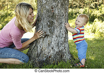 little boy playing with his mother in nature