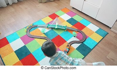 A little boy plays in the train, running after him to overtake