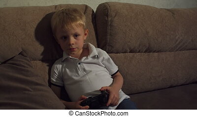 A little boy plays video games at night sitting on the couch with big pillows.