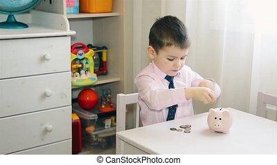 A little boy puts money in a piggy Bank