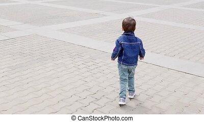 a little boy running around the road runs