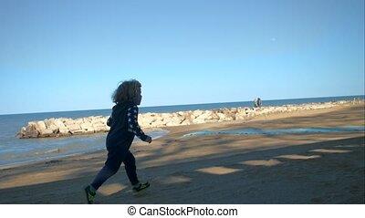 A little boy runs along the seashore.