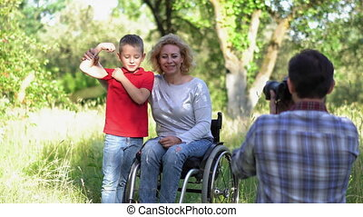 A little boy showing his biceps posing with mother in a wheel chair.