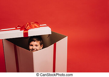 A little boy sits in a Christmas present and looks out of it on a red background