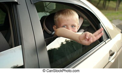 A little boy sits in the backseat of a car, he looks out the window and smiles.