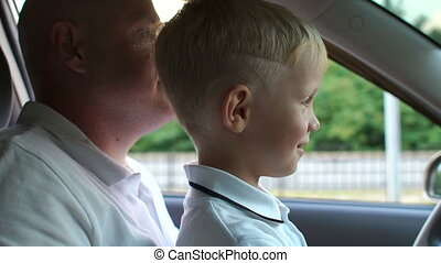 A little boy sits with his father behind the wheel of a car, learning to drive.