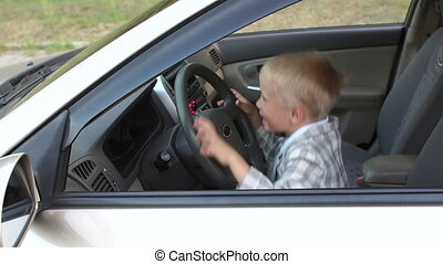 A little boy sitting behind the wheel of a car, he makes music louder and dance.