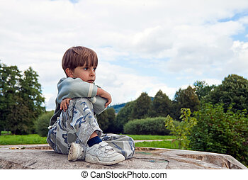 A little boy sitting on a felled tree