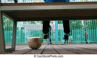 A little boy sitting on the bench and watching other kids playing football