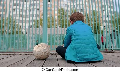 A little boy sitting on the bench near the deflated ball and watching other kids playing football