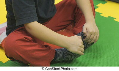 A little boy sitting on the floor in kindergarten - A little...