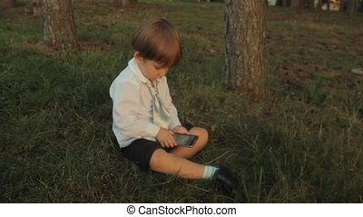 A little boy sitting on the green grass and playing with a smartphone in the park. Sunset in summer.