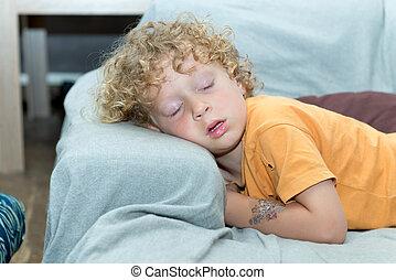 little boy sleeping on the sofa
