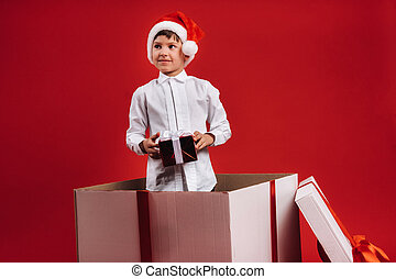 A little boy stands in a gift box with a Christmas present in his hands