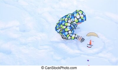 A little boy tries to take out a slippery nose from a snowman