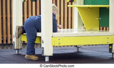 A little boy trying to climb in house on the playground.