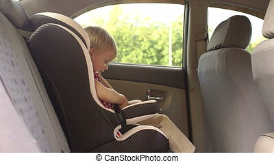 A little boy unbuttons his seat belts in a child car seat in the car.