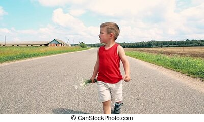 A little boy with a bouquet of daisies is on the road