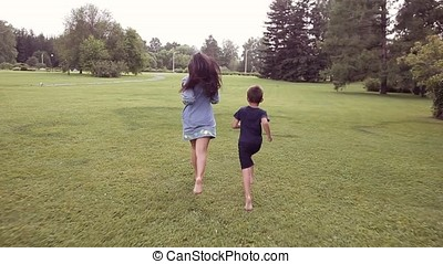 A Little boy with a girl running on the grass smiling and jumping in a good mood