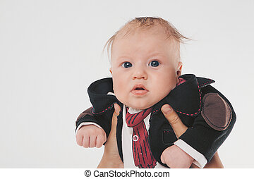 A little boy with black eyes in a business suit holding hands