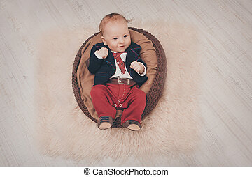 A little boy with black eyes in a business suit lies clenching his fists in a brown cradle