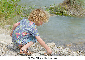 little boy with blond hair plays the waterside