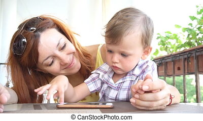 a little boy with mom uses the Internet on Smartphone