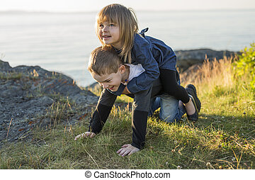 Little brother and sister playing in the grass on sunset in summer