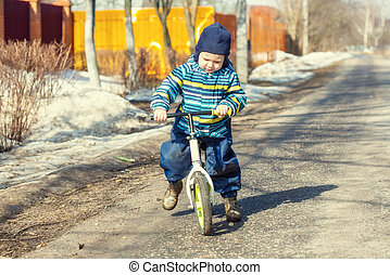 A little Caucasian boy 2 years old learns to ride a balance bike
