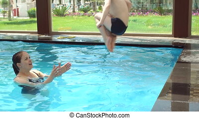 A little cheerful boy jumps into the pool, his mother catches him. Slow motion.