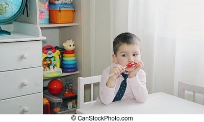 A little child eats candy red HD 1920
