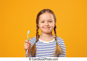 A little child girl in a striped pajamas holding a toothbrush. The concept of daily hygiene. Yellow background.