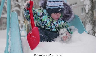 A little child playing with snow in winter Park. Sunny winter's day. Fun and games in the fresh air.