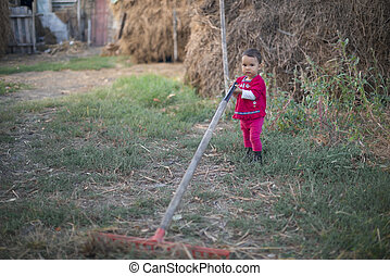 A little country girl working with a rake