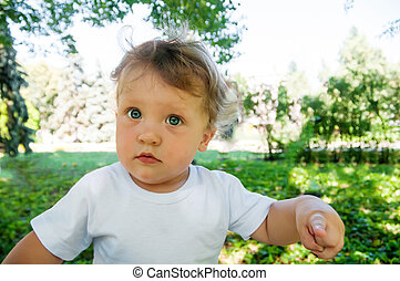 a little curly boy in a white T-shirt looks directly at me and shows a finger, in the street in the summer, closeup