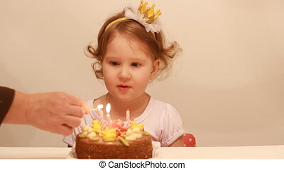 a little cute baby looks at the candle flame on the birthday cake. The concept of a children's holiday