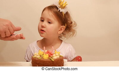 a little cute baby looks at the candle on the birthday cake. The concept of a children's holiday