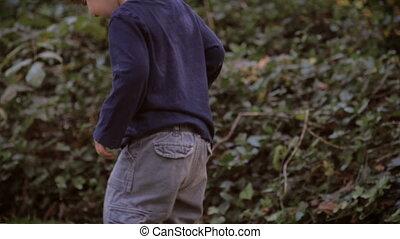 A little cute boy with baggy pants walking in grass in slow...