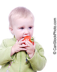 A little cute girl eating tomato