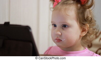 A little cute girl eats food and watches cartoons on the tablet. Child and gadgets, applications, internet, games. Close-up.