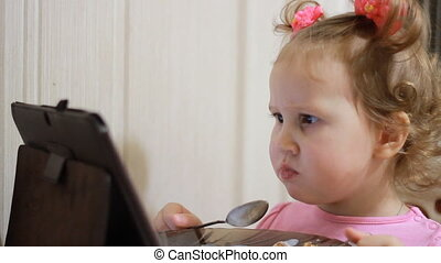 A little cute girl eats food and watches cartoons on the tablet. Child and gadgets, applications, internet, games.