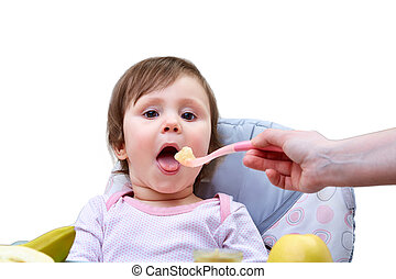 A little cute girl is fed with a spoon of fruit puree on the white background.