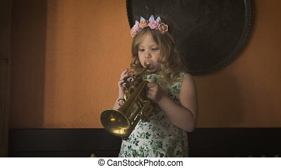 Music - life. A little beauiful girl is playing saxophone in the cozy cafe. A sweet little blondie is playing instrument in the cozy cafe.