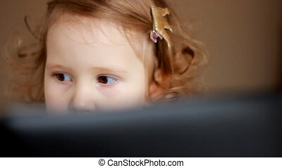 A little cute girl looks at the screen monitor computer or laptop. Funny child looking tv, video,cartoon or playing the game. Eyes close up.
