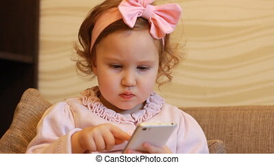 A little cute girl sitting in sofa in a living room, looking cartoon and playing the game. Funny child looks at the phone screen and plays downloaded application on a smart phone. Close-up