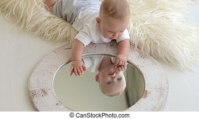 A little five-month newborn baby is playing with a mirror at home lying on bed.