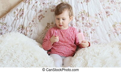 A little funny darling combs the blonde hair comb. The concept of child hygiene.
